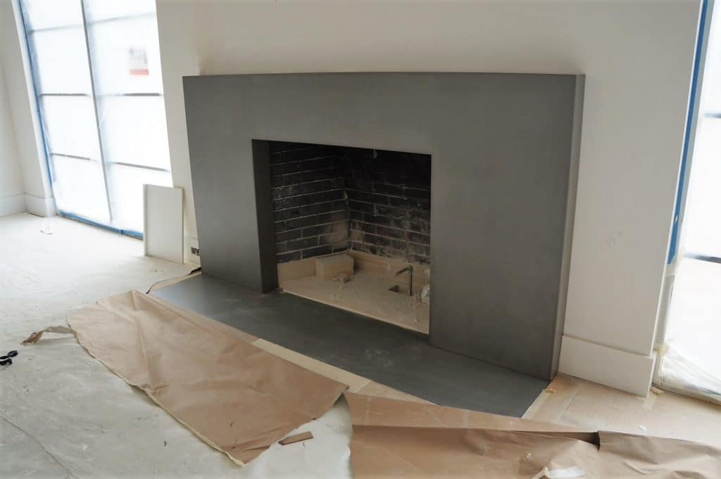 Large Gray Concrete Fireplace Surround with matching hearth set into the floor installed in Dallas, Tx