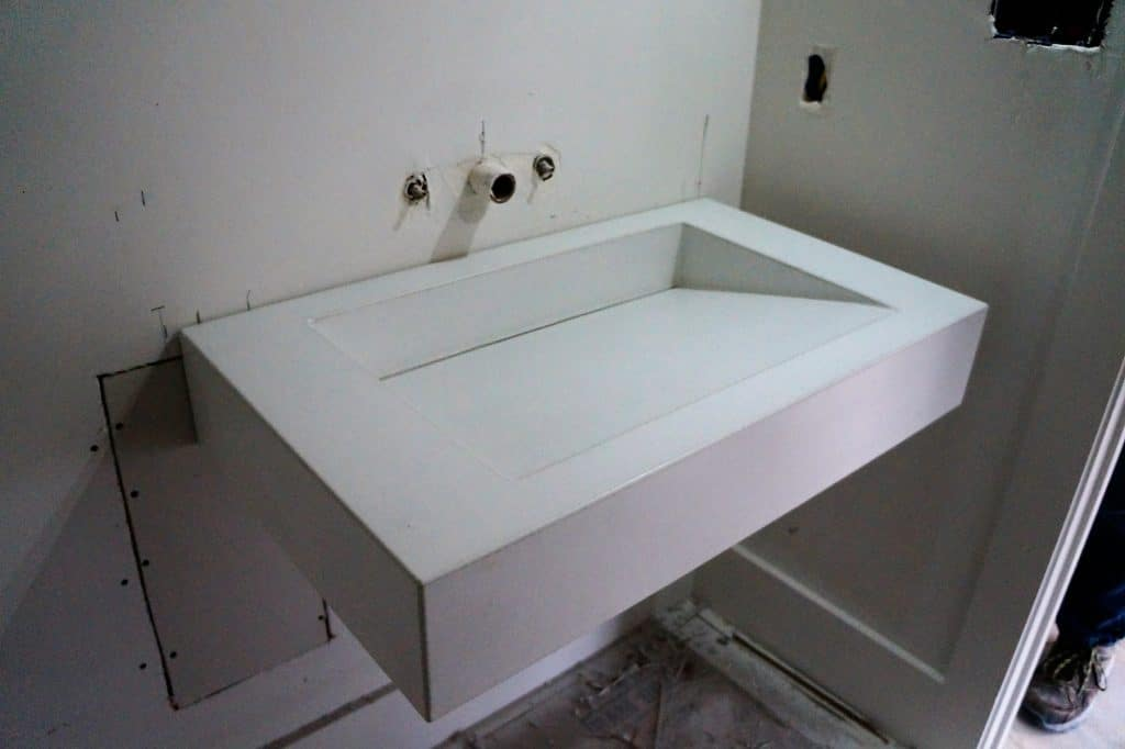 All white floating ramp sink with custom slot drain for a home in Dallas, Tx