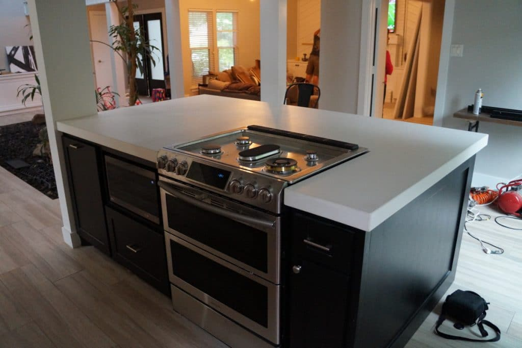 This kitchen also include this large white concrete island, which is a great contrast to add to the grey perimeter countertops