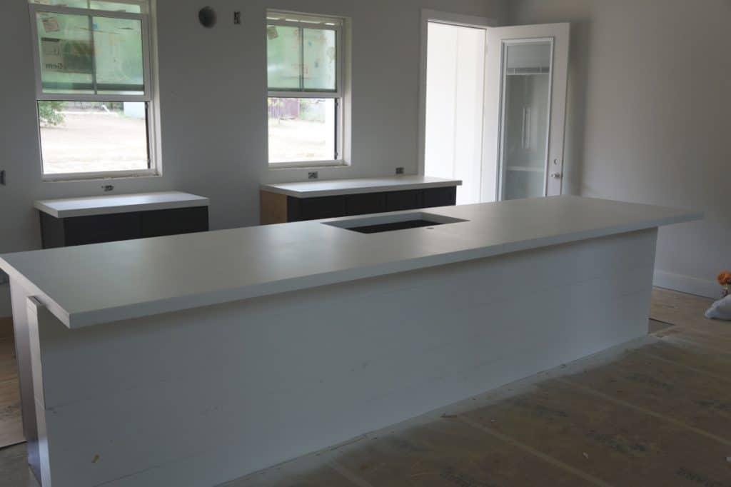 Giant white concrete island for this open kitchen