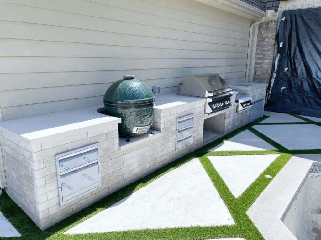 Large outdoor kitchen with concrete countertops, green egg smoker and grill