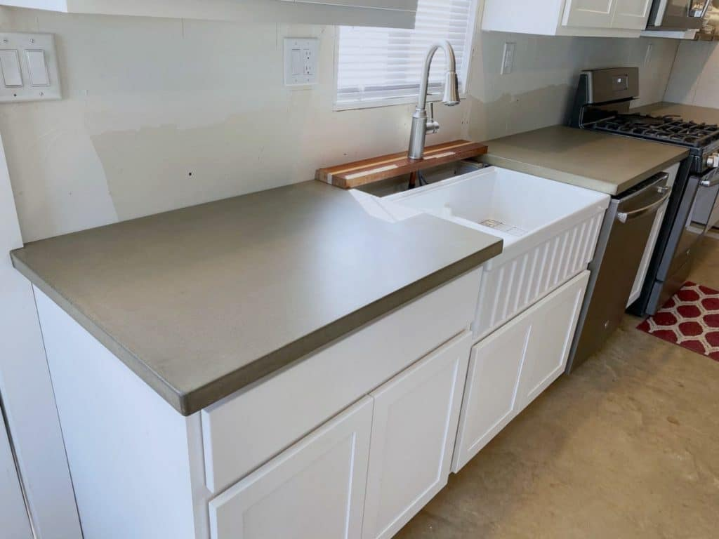 Beige Concrete Countertops Paired with a White Farm Sink