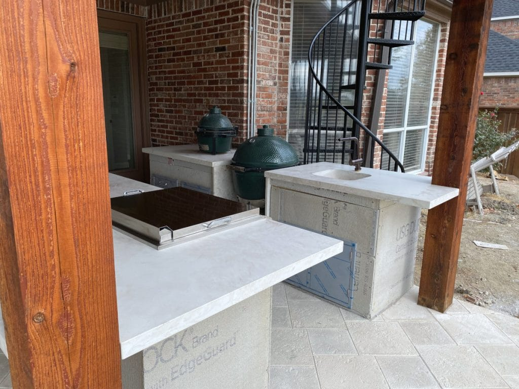 This Outdoor Kitchen is Completed with a Custom Concrete Sink, 2 Big Green Egg Smokers, and a Flat Top Grill