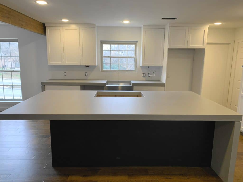 "Beautiful kitchen with 3"" thick light grey concrete countertops and waterfall panels"