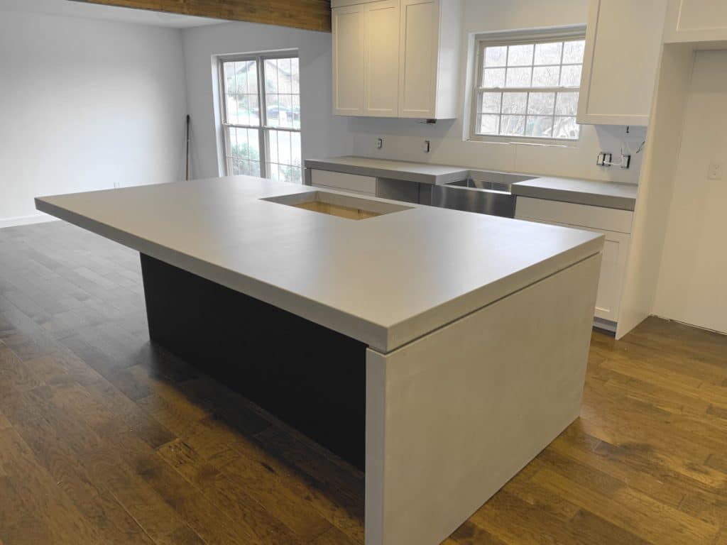 Thick Light Grey Concrete Kitchen Island With Waterfall Panel