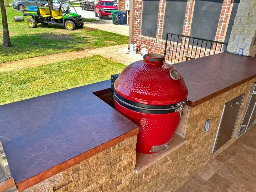 Custom stained concrete countertops and matching red egg smoker