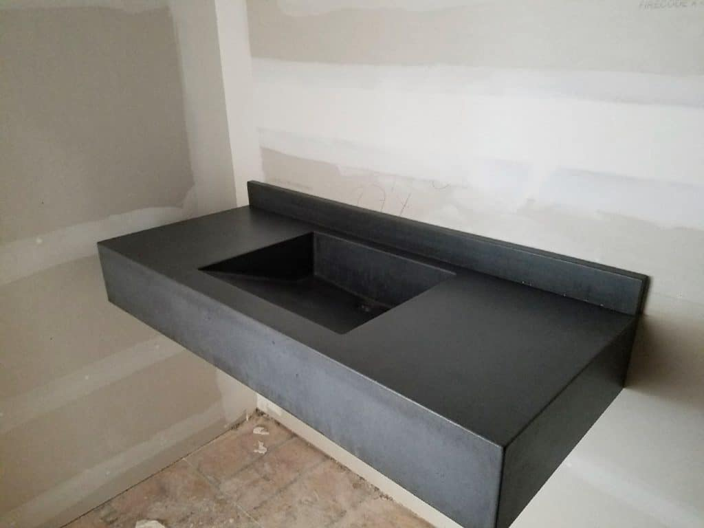 Dark grey floating concrete sink with matching backsplash.