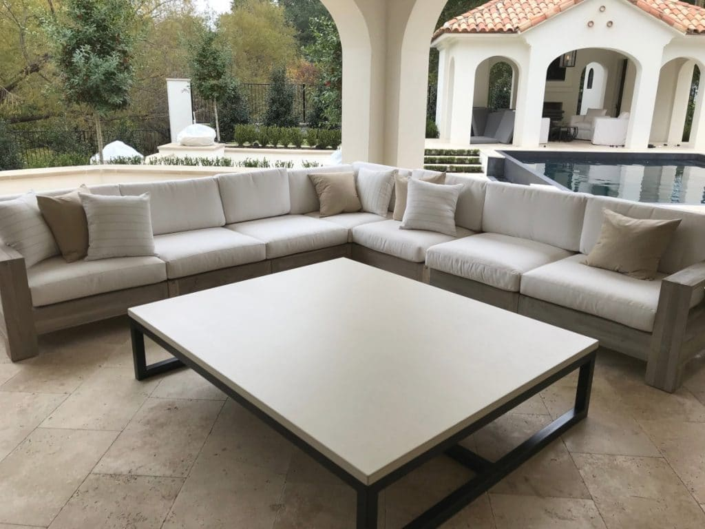 A beautiful light tan concrete table that is the center piece of this outdoor living space.