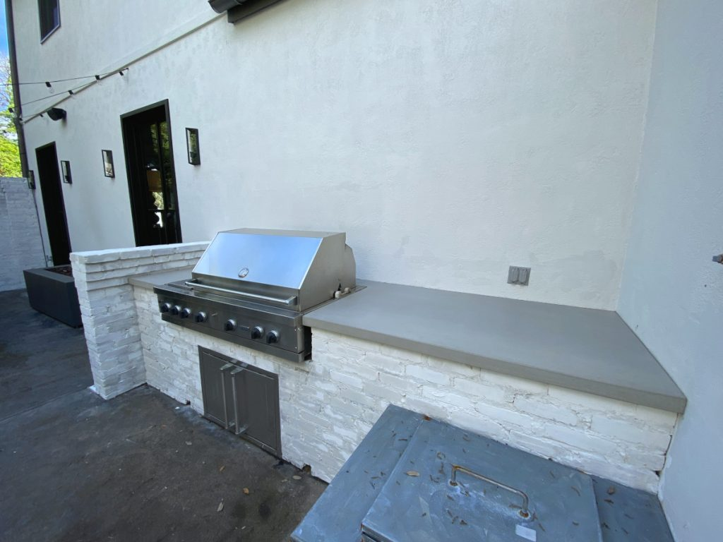 Grey Concrete Countertop on Top of White Brick for an Outdoor Kitchen