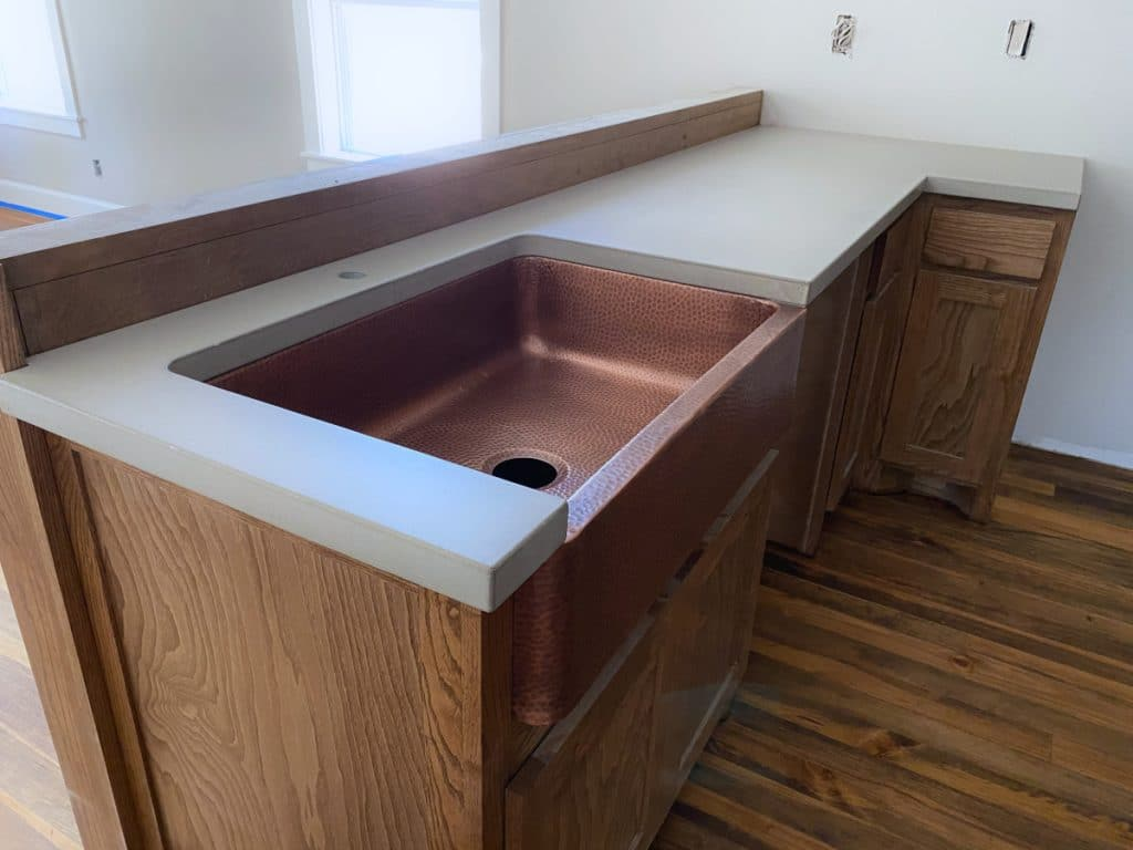 Beautiful Light Grey Concrete Countertop Paired with a Hammered Copper Farm Sink