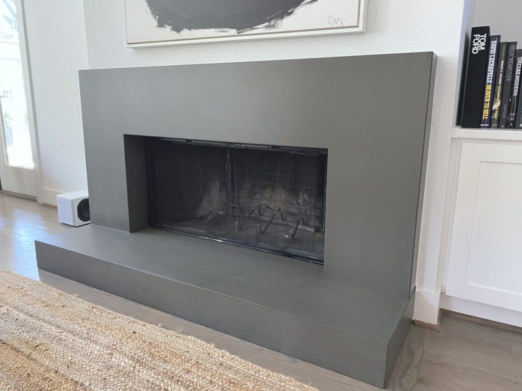Large Grey Concrete Fireplace Surround and Hearth That Has Become the Center Piece of This Living Room for a home in Dallas, Tx