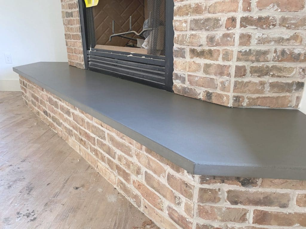 Large Grey Concrete Fireplace Hearth Paired with a Beautiful Brick Fireplace