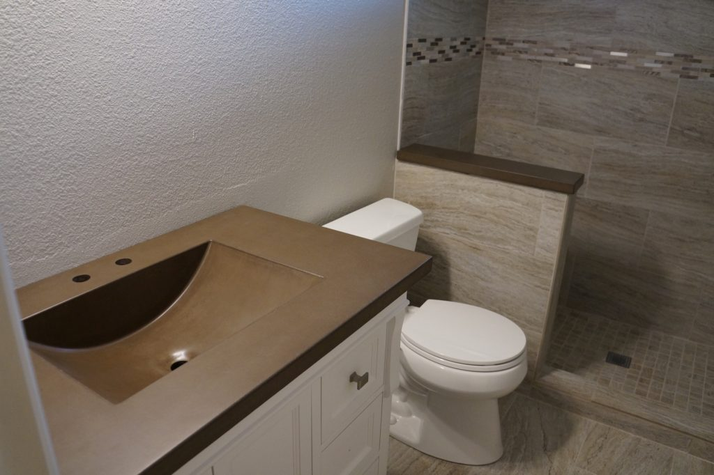 Brown Concrete Vanity top and wall topper. The sink is our integral barrel sink. This was installed in Corinth, Texas