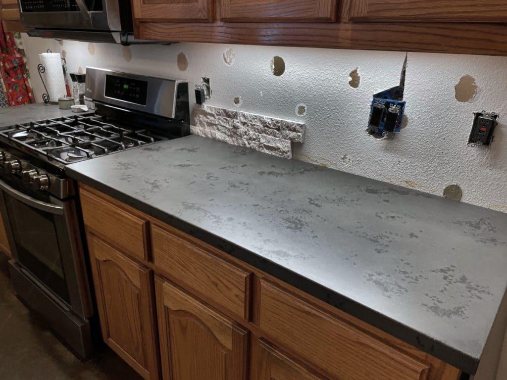 Custom dark two tone concrete countertops near the stove