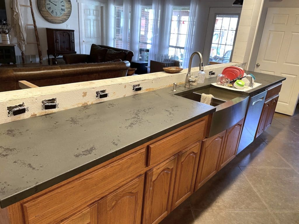 Custom dark two tone concrete countertops with stainless steel farm sink