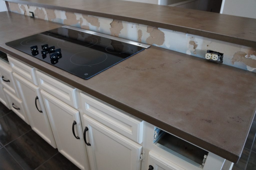 Brown with dark Brown fill, Kitchen Countertops with cooktop and pop-up down draft installed.